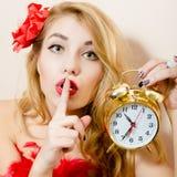Schöner Zauber des Weckers junge blonde Pinupfrau im roten Kleid halten, das Ruhe zeigt, unterzeichnen Sie u. Betrachten der Kame Lizenzfreie Stockfotos