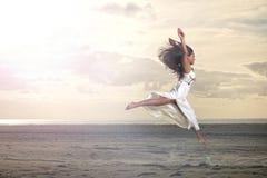 Schönes afrikanisches Mädchen, das in weißes Kleid springt Lizenzfreies Stockfoto