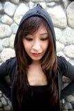 Schönes asiatisches Mädchen, das eine Haube trägt Stockbilder