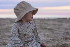 Schönes Baby, das bei dem Sonnenuntergang anstarrt Lizenzfreie Stockfotografie
