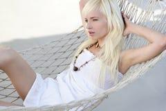Schönes blondes junges Mädchen entspannte sich auf Hängematte Stockfotografie