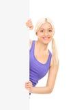 Schönes blondes Mädchen, das hinter einer Leerplatte aufwirft Stockfoto