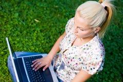 Schönes blondes Mädchen, das Laptop in der Natur verwendet. Stockfotografie