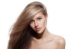 Schönes blondes Mädchen. Gesundes langes Haar. Weißer Hintergrund Lizenzfreies Stockfoto