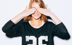 Schönes blondes verrücktes Mädchen des lustigen Lebensstilporträts schließt Augen mit ihren Händen, im Sweatshirt und in den weiß Lizenzfreies Stockbild