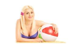 Schönes blondes weibliches Lügen auf einem Badetuch und Halten eines Balls Lizenzfreie Stockfotos