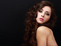 Schönes braunes Frauenschauen des gelockten Haares Nahaufnahme auf schwarzem Hintergrund Stockfotos