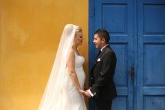 Schönes Braut- und Bräutigamhändchenhalten nähert sich bunter Tür und Wand Stockfotos