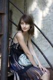 Schönes Brunettemädchen, das auf den Treppen im Freien sitzt Stockfotos