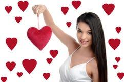 Schönes Brunettemädchen, das ein rotes Herz hält. Glückliche Frau, Valentinstag. Stockfotos