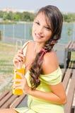 Schönes Brunettemädchen, das eine Plastikflasche mit Orangensaft hält. Lizenzfreies Stockbild