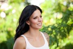 Schönes Brunettemädchen, das im Park sich entspannt Stockbilder