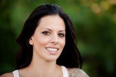 Schönes Brunettemädchen, das im Park sich entspannt Lizenzfreie Stockbilder