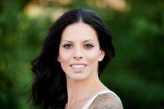 Schönes Brunettemädchen, das im Park sich entspannt Lizenzfreie Stockfotografie