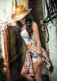 Schönes Brunettemädchen mit Landblick, schoss zuhause in der stabilen, rustikalen Art Attraktive Frau mit Cowboyhut, Denimkurze h Stockbild