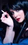 Schönes Brunettemädchen mit Zigarette und Gewehr Stockbilder