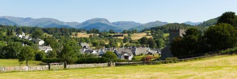 Schönes englisches Bauerndorf des Hawkshead See-Bezirkes Cumbria Großbritannien im Sommer mit Kirchenpanorama des blauen Himmels Lizenzfreie Stockfotografie