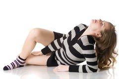 Schönes entspanntes Mädchen, das auf dem Fußboden liegt Stockfotos