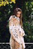 Schönes europäisches Mädchen im Luxusluchspelzmantel, der draußen aufwirft Stockfotografie