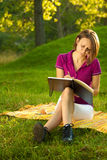 Schönes Frauenschreiben in ihrem Tagebuch im Park Lizenzfreie Stockfotografie