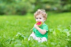 Schönes gelocktes Baby, das Wassermelonensüßigkeit isst Lizenzfreie Stockfotografie