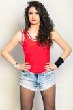 Schönes gelocktes Haar der jungen Frau, kurze Jeanshose und rotes Trägershirt Lizenzfreies Stockbild