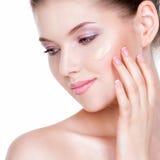 Schönes Gesicht der jungen Frau mit kosmetischer Grundlage auf einer Haut Stockfotos