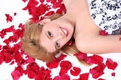 Schönes jugendlich Mädchen, das auf Rosen-Blumenblatt über Weiß legt Stockfotos