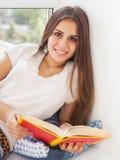 Schönes jugendlich Mädchen, das ein Buch liest Lizenzfreie Stockfotos