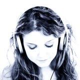 Schönes jugendlich Mädchen, das zu den Kopfhörern hört Lizenzfreie Stockfotos
