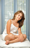 Schönes jugendlich Mädchen zu Hause im weißen Kleid Stockbilder