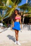 Schönes jugendliches schwarzes Mädchen in der Sonnenbrille, im BH und im Rock Stockfoto