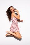 Schönes jugendliches vorbildliches Brunette-Mädchen im weißen Kleid, das auf weißen Hintergrund mit rotem Lutscher springt innen  Lizenzfreies Stockbild