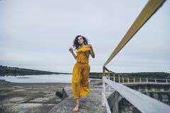 Schönes junges glückliches Mädchen geht entlang das Geländer eines Betrugs Stockbild
