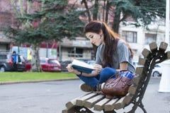 Schönes junges Glückmädchen, das auf Bank- und Lesebuch sitzt Stockbild