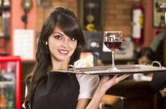 Schönes junges Kellnerinmädchen, das ein Getränk dient Stockfotografie