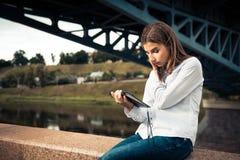 Schönes junges Mädchen, das digitale Tablette verwendet Stockfotos