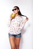 Schönes junges Mädchen, das im Studio auf einem weißen Hintergrund aufwirft Trinkender Orangensaft Stockfotos