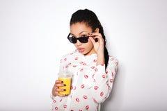 Schönes junges Mädchen, das im Studio auf einem weißen Hintergrund aufwirft Trinkender Orangensaft Stockfotografie