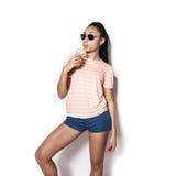 Schönes junges Mädchen, das im Studio auf einem weißen Hintergrund aufwirft Trinkender Orangensaft Lizenzfreies Stockbild