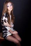 Schönes junges Mädchen in einem Fantasiemake-up, das im Studio auf einem Stuhl auf einem schwarzen Hintergrund sitzt Lizenzfreie Stockfotos