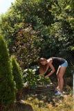 Schönes junges Mädchen malt einen hölzernen Gazebo Sommerarbeit im Garten Schöner Brunette beschichtet Holzbalken Stockfoto