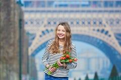 Schönes junges Mädchen mit roten Tulpen nahe dem Eiffelturm Stockfoto