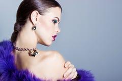 Schönes junges Mädchen mit schönem stilvollem teurem Schmuck, Halskette, Ohrringe, Armband, Ring, filmend im Studio Stockbild