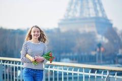 Schönes junges Mädchen mit Stangenbrot und Tulpen nahe dem Eiffelturm Stockfotografie