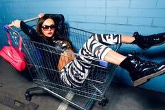 Schönes junges sexy Mädchen, das den Spaß sitzt im Einkaufslaufkatzenwarenkorb nahe blauer Wand in der Sonnenbrille, rosa Rucksac Stockfotografie