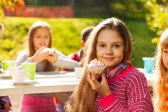Schönes kleines Mädchen, das kleinen Kuchen und Freunde hält Lizenzfreie Stockfotos