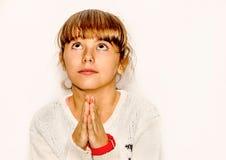 Schönes kleines Mädchen, das oben, lokalisiert auf Weiß betet und schaut Lizenzfreies Stockbild