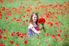 Schönes kleines Mädchen, das rote Mohnblumen auswählt Stockfoto