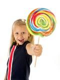 Schönes kleines weibliches Kind mit den süßen blauen Augen, die das enorme Lutscherspiralen-Süßigkeitslächeln glücklich halten Lizenzfreies Stockfoto